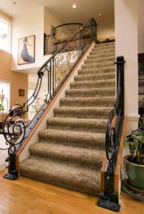 Деревянная лестница с кованными перилами на второй этаж